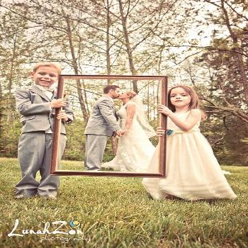 A Love-ly work of art! Ring-bearer and flower girl hold up a frame to